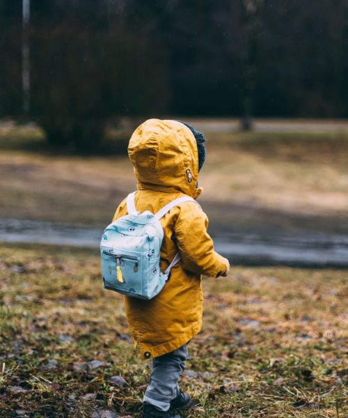 kid in raincoat walking near stream