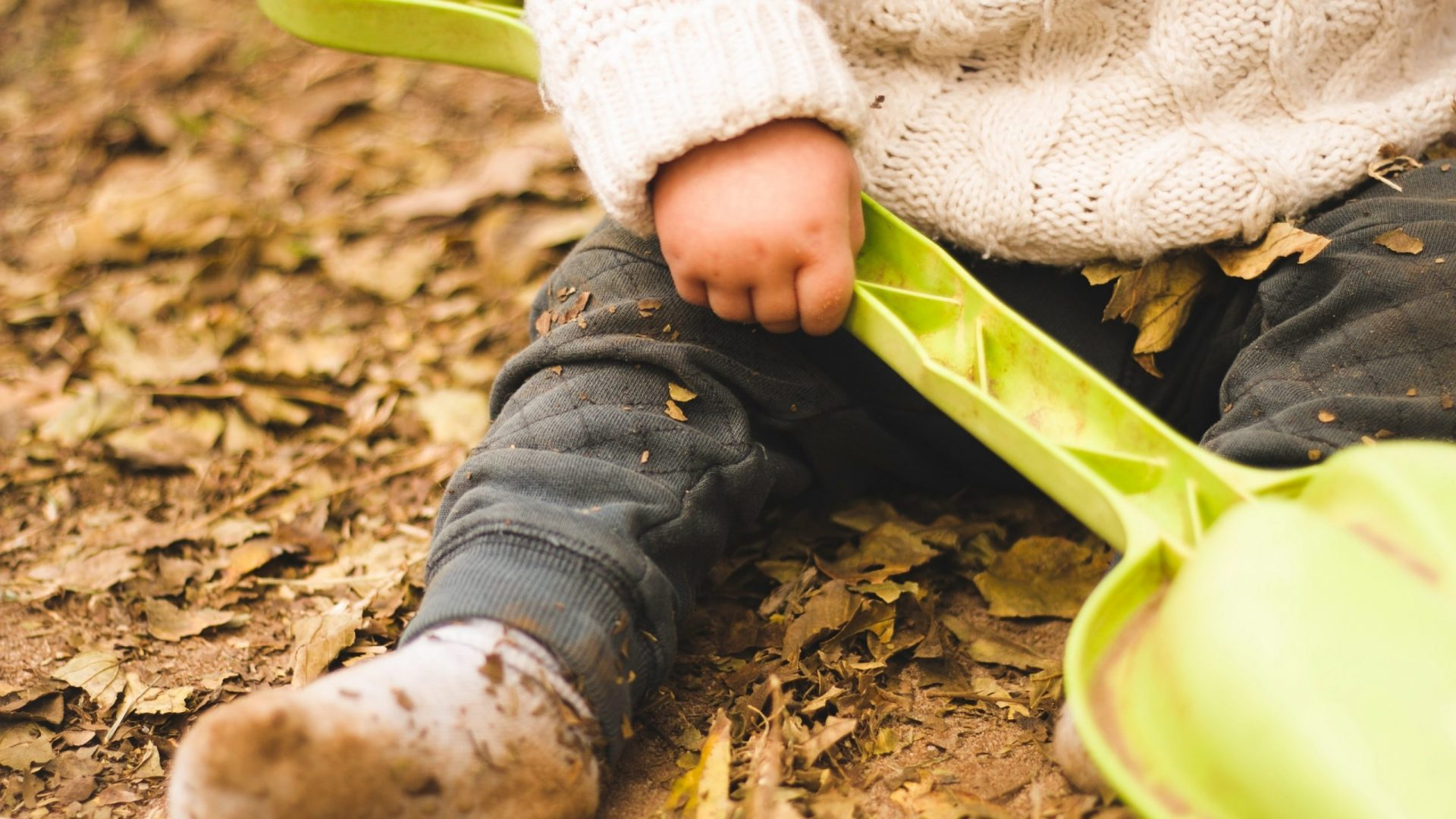 toddler with leaves on socks holding shovel